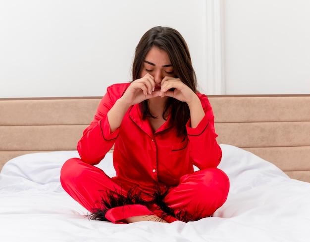 Mulher bonita jovem triste de pijama vermelho, sentada na cama, chorando no interior do quarto, sobre fundo claro