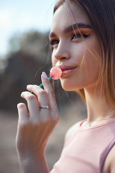 Mulher bonita lambendo um close-up de pirulito. sombras vermelhas nos olhos de uma menina, maquiagem profissional, cosméticos naturais