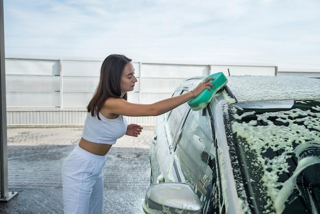 Mulher bonita lavando espuma com esponja verde limpando o carro da sujeira