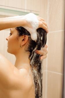 Mulher bonita, lavar o cabelo com o shampoo