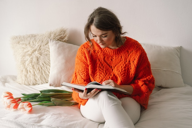 Mulher bonita lendo livro na cama em casa. mulher se alegra com as tulipas.