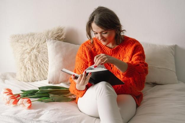Mulher bonita lendo livro na cama em casa.