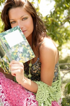 Mulher bonita, lendo um livro na floresta, natureza