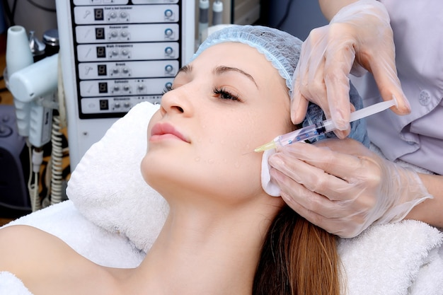 Mulher bonita leva uma injeção na cara.