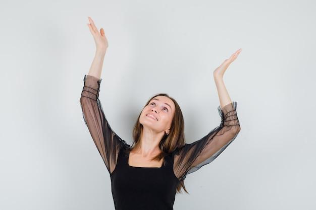 Mulher bonita levantando os braços com as palmas das mãos abertas enquanto olha para cima com uma blusa preta e parece alegre