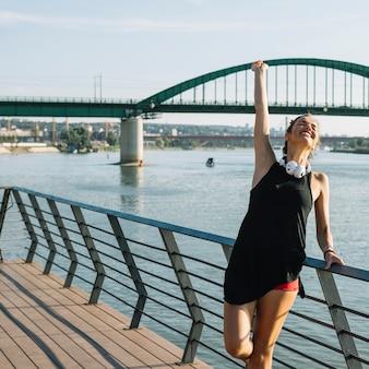 Mulher bonita, levantando os braços em pé perto do rio