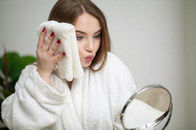 Mulher bonita, limpando a pele do rosto com uma toalha depois de lavar o retrato do rosto.