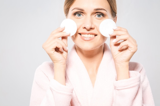 Mulher bonita limpando o rosto com uma almofada de algodão