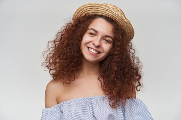 Mulher bonita, linda garota com cabelo ruivo cacheado. usando blusa listrada de ombros largos e chapéu. incline a cabeça e sorria. close up, isolado sobre a parede branca