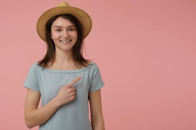 Mulher bonita, linda garota com longos cabelos castanhos. vestindo camiseta e chapéu azulados, sorrindo. apontando para a direita no espaço da cópia sobre a parede rosa pastel