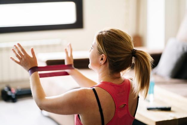 Mulher bonita loira atleta caucasiano fazendo exercícios com elástico na sala de estar em casa