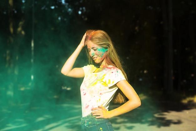 Mulher bonita loira brincando com tinta verde seca holi no parque