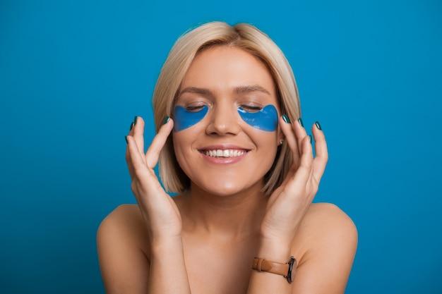 Mulher bonita loira caucasiana sem roupas está aplicando uma máscara no rosto enquanto sorri alegremente e posa sobre um fundo azul
