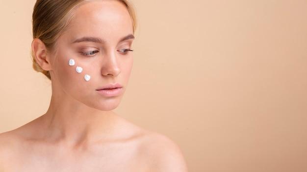 Mulher bonita loira close-up com creme no rosto