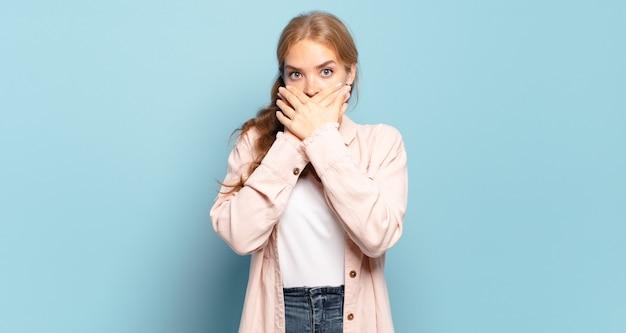 Mulher bonita loira cobrindo a boca com as mãos com uma expressão chocada e surpresa, mantendo um segredo ou dizendo oops