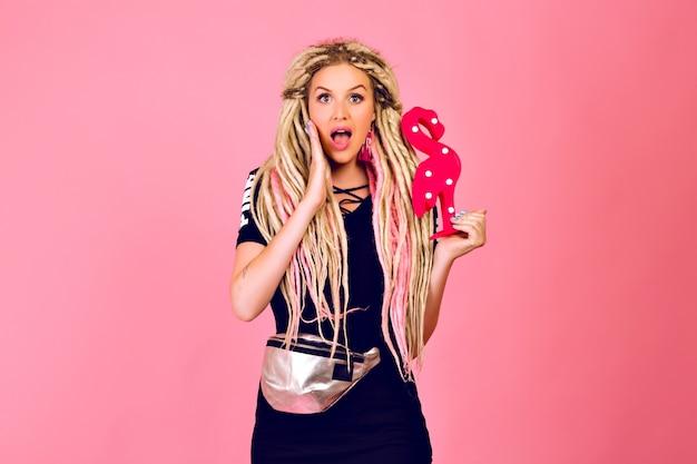 Mulher bonita loira com longos dreads loira segurando flamingo de plástico, vestindo roupa elegante esporte chique, emoções surpreendidas, último estilo pop.