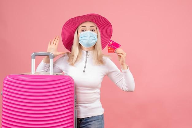Mulher bonita loira com máscara em pé perto da mala.