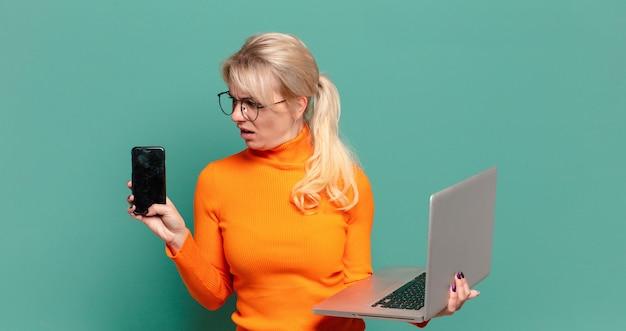 Mulher bonita loira com um celular e um laptop