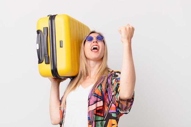 Mulher bonita loira com uma mala. conceito de verão