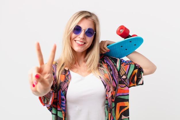 Mulher bonita loira com uma placa de skate. conceito de verão