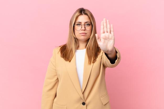 Mulher bonita loira curvilínea olhando séria mostrando a palma da mão aberta fazendo gesto de pare