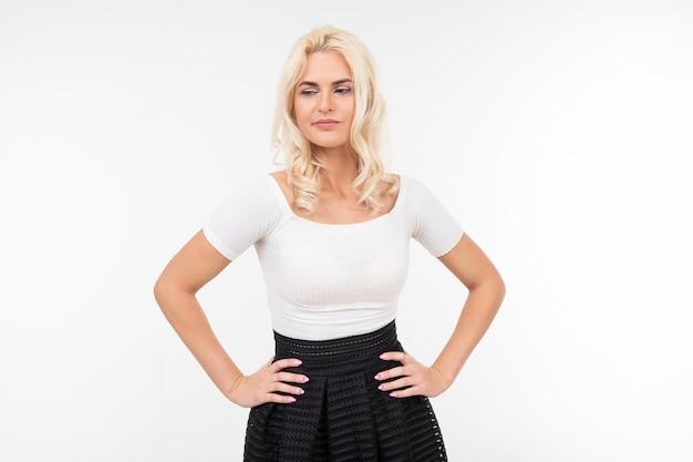 Mulher bonita loira de camiseta branca posando com as mãos nos quadris, sobre um fundo branco