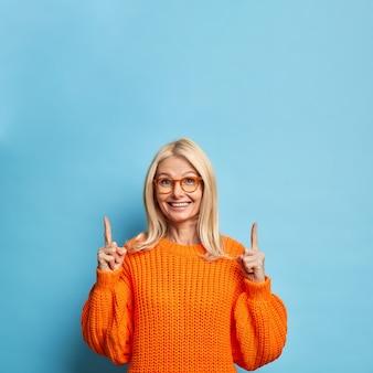 Mulher bonita loira de quarenta anos sorri alegremente apontando para o espaço da cópia, usa suéter laranja de óculos.