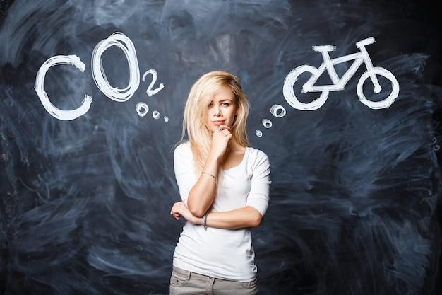 Mulher bonita loira escolhe entre poluição por co2 da natureza e transporte saudável de bicicleta