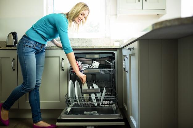 Mulher bonita loira esvaziando a máquina de lavar louça