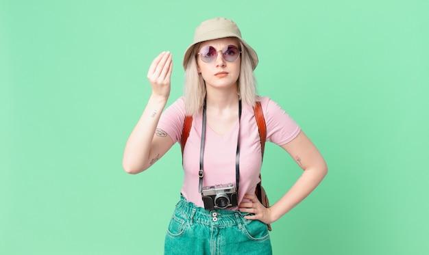 Mulher bonita loira fazendo capice ou gesto de dinheiro, dizendo para você pagar. conceito de verão
