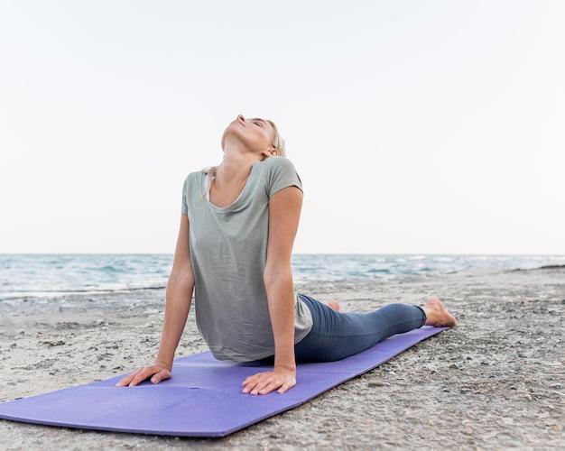 Mulher bonita loira fazendo ioga na praia