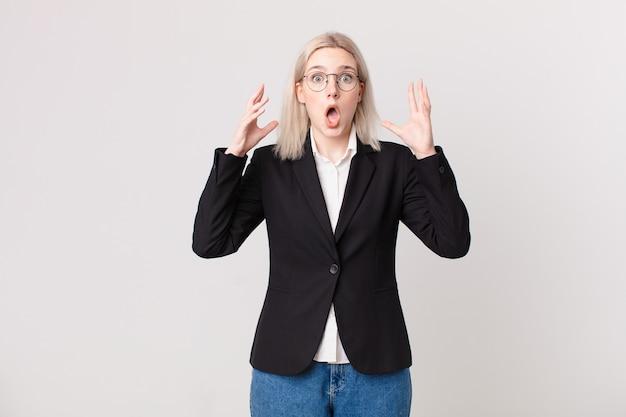Mulher bonita loira gritando com as mãos no ar. conceito de negócios