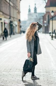 Mulher bonita loira jovem andando na rua da cidade. tempo ensolarado