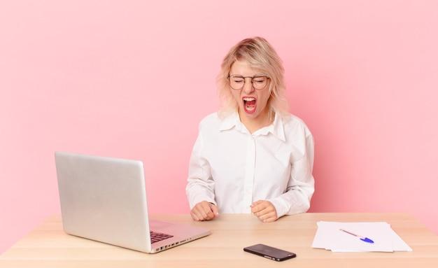 Mulher bonita loira jovem bonita mulher gritando agressivamente, parecendo muito zangado. conceito de mesa de trabalho
