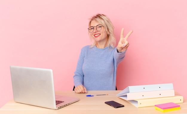 Mulher bonita loira jovem bonita mulher sorrindo e parecendo feliz, gesticulando vitória ou paz. conceito de mesa de trabalho