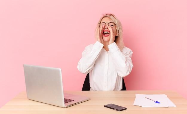 Mulher bonita loira jovem bonita se sentindo feliz, dando um grande grito com as mãos ao lado da boca. conceito de mesa de trabalho
