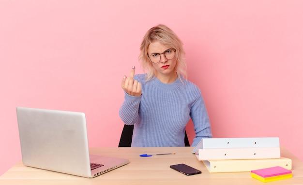 Mulher bonita loira jovem bonita sentindo-se zangada, irritada, rebelde e agressiva. conceito de mesa de trabalho