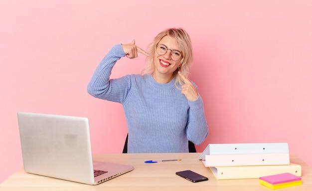 Mulher bonita loira jovem bonita sorrindo com confiança, apontando para o próprio sorriso largo. conceito de mesa de trabalho