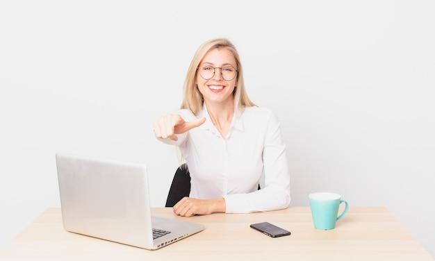 Mulher bonita loira jovem loira apontando para a câmera escolhendo você e trabalhando com um laptop