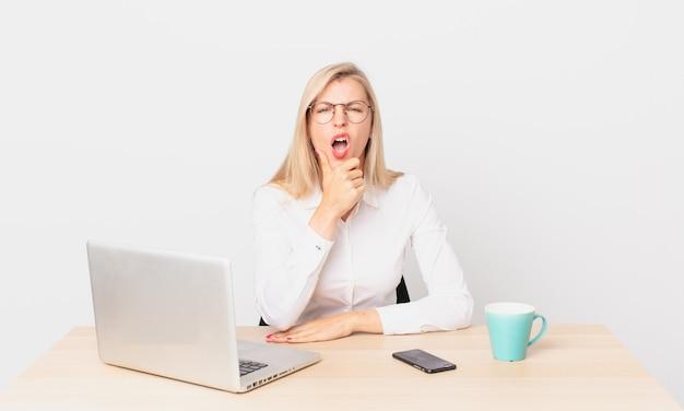 Mulher bonita loira jovem loira com a boca e os olhos bem abertos, a mão no queixo e trabalhando com um laptop