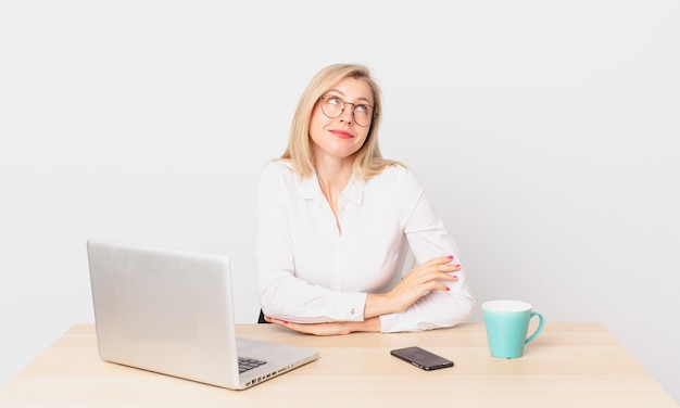 Mulher bonita loira jovem loira dando de ombros, sentindo-se confusa e insegura e trabalhando com um laptop