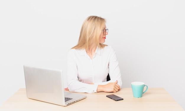 Mulher bonita loira jovem loira em vista de perfil pensando, imaginando ou sonhando acordada e trabalhando com um laptop