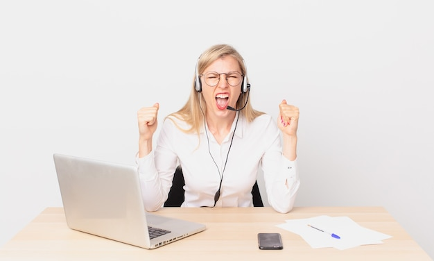 Mulher bonita loira jovem loira gritando agressivamente com uma expressão de raiva e trabalhando com um laptop