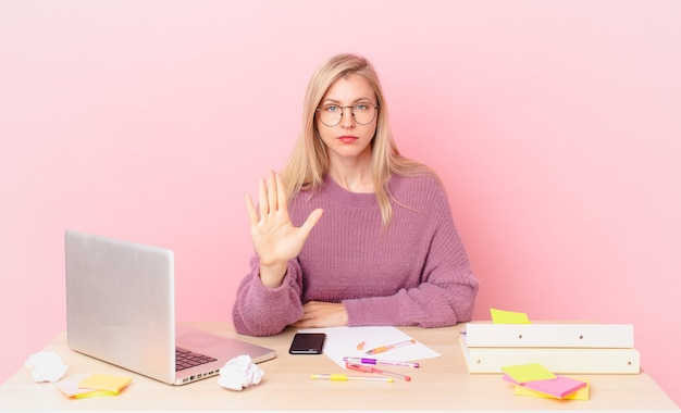 Mulher bonita loira jovem loira olhando séria, mostrando a palma da mão aberta, fazendo um gesto de parada e trabalhando com um laptop