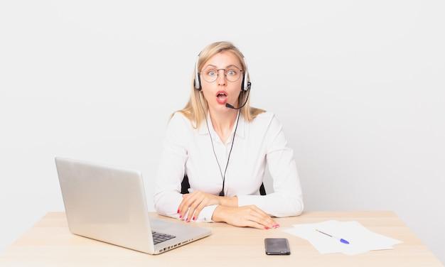 Mulher bonita loira jovem loira parecendo muito chocada ou surpresa e trabalhando com um laptop