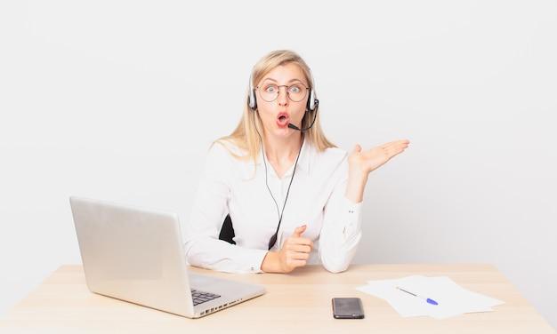 Mulher bonita loira jovem loira parecendo surpresa e chocada, com o queixo caído segurando um objeto e trabalhando com um laptop
