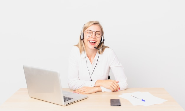 Mulher bonita loira jovem loira rindo alto de uma piada hilária e trabalhando com um laptop