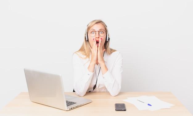 Mulher bonita loira jovem loira se sentindo chocada e com medo e trabalhando com um laptop