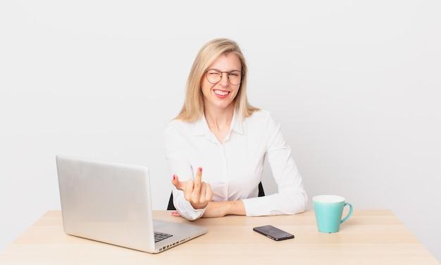 Mulher bonita loira jovem loira se sentindo irritada, irritada, rebelde e agressiva e trabalhando com um laptop