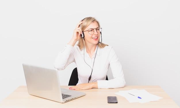Mulher bonita loira jovem loira se sentindo perplexa e confusa, coçando a cabeça e trabalhando com um laptop